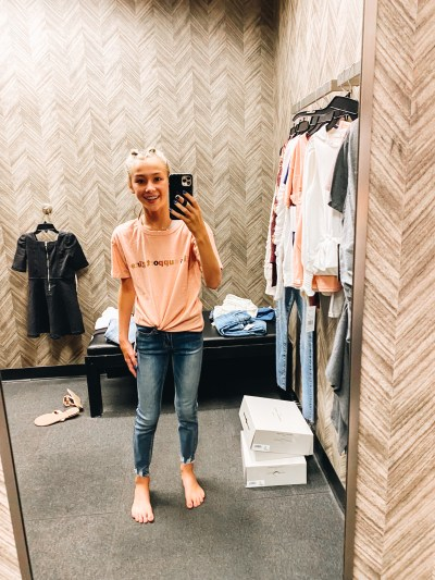 Nordstrom Anniversary Sale 2021: Try On Edition featured by top Pittsburgh fashion blogger, Fashionably Late Mom   Nordstrom Anniversary Sale by popular Pittsburgh fashion blog, Fashionably Late Mom: image of a teenage girl wearing a Nordstrom peach colored graphic t-shirt and jeans.