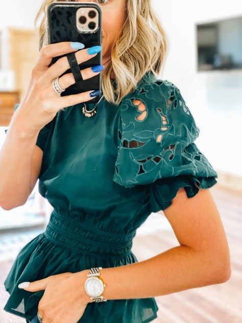 puff sleeve top, eyelet sleeves, blouse, fall style, working mom fashion | Working Mom Outfits by popular Pittsburgh fashion blog, Fashionably Late Mom: image of a woman wearing a dark green puff sleeve peplum top.