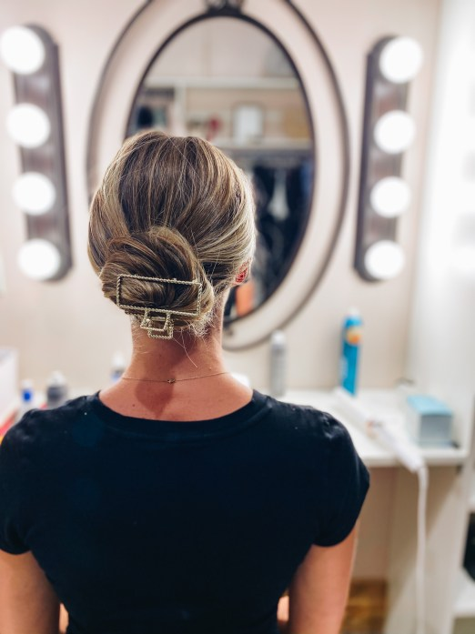 Claw Clip Hairstyles by popular Pittsburgh fashion blog, Fashionably Late Mom: image of a woman putting a claw clip in her hair.