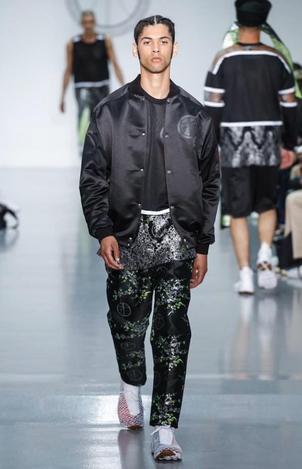 """According to Danish-born designer Astrid Andersen, present day street culture is a universal language. Her collection, set against the heady back alleys of the Shanghai metropolis and the hip-hop beats of Harlem, amplifies this borderless appeal. Andersen's Spring/Summer 16 collection is a whirlwind of cultural references – both urban and ethnic – melded into one monolithic offer that could only be described as """"sensitive thug."""" Oversized basketball silhouettes blended with delicate Chantilly lace; the once hyper-masculine hip-hop infused male is finally baring his soft spot."""