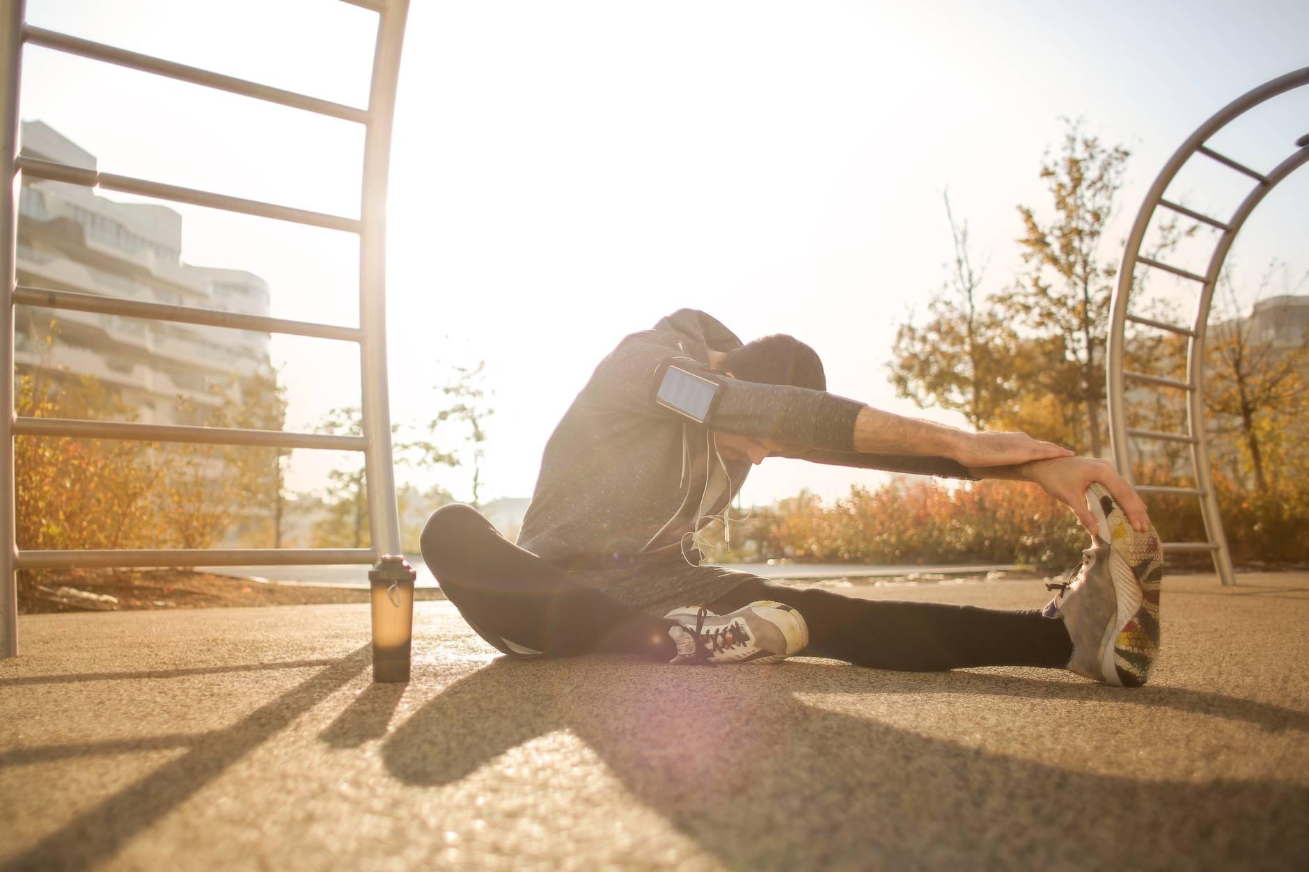 flexible sportsman stretching on sports ground