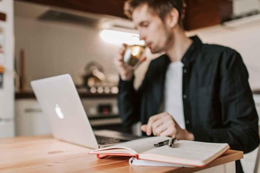 crop male freelancer drinking water while watching laptop in kitchen