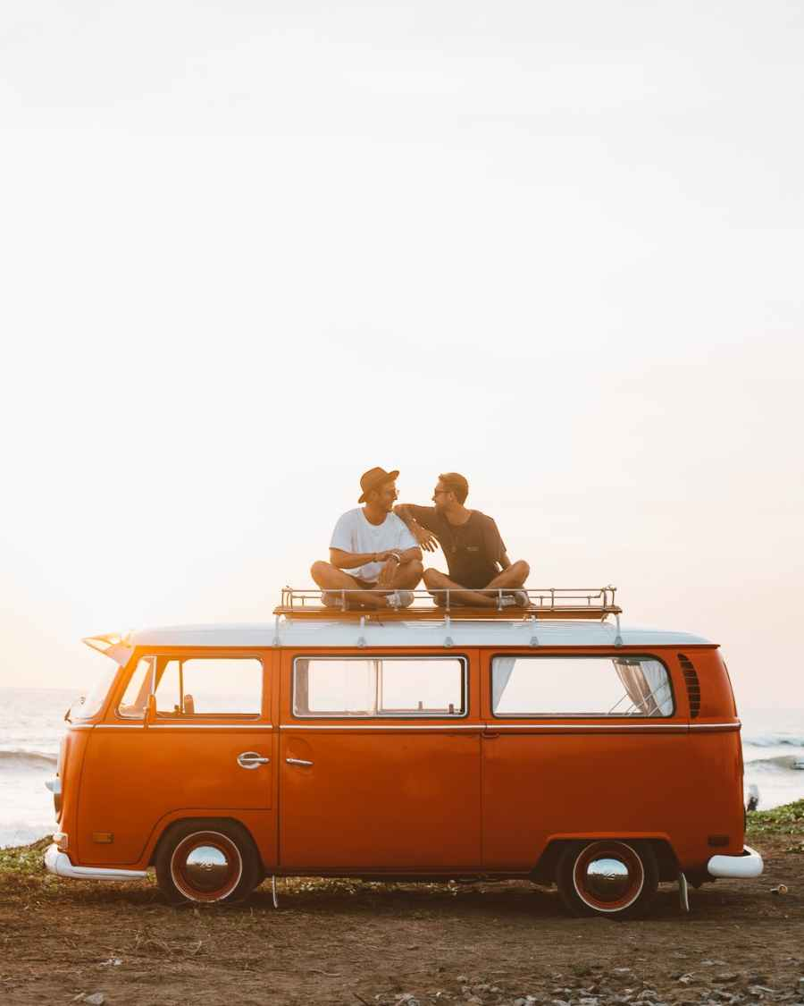 happy friends on camper van roof. Photo by ROMAN ODINTSOV on Pexels.com