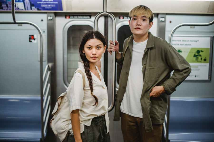 trendy young asian couple holding handrail while commuting by subway train