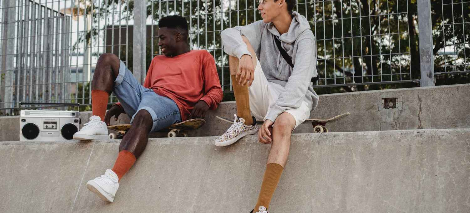 cheerful men with skateboards resting om ramp