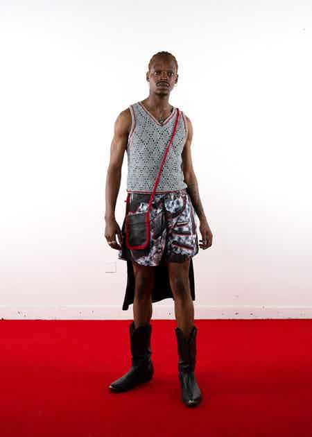 Look 01 featuring the George Vest, a lace hole crochet vest made entirely from shredded t-shirts.