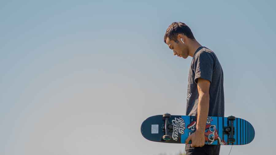 man holding a skateboard. Photo by Feruzbek Matkarimov on Pexels.com