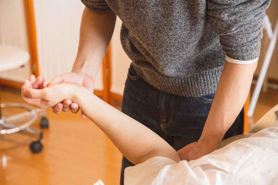 crop chiropractor massaging hand of patient. Photo by Ryutaro Tsukata on Pexels.com