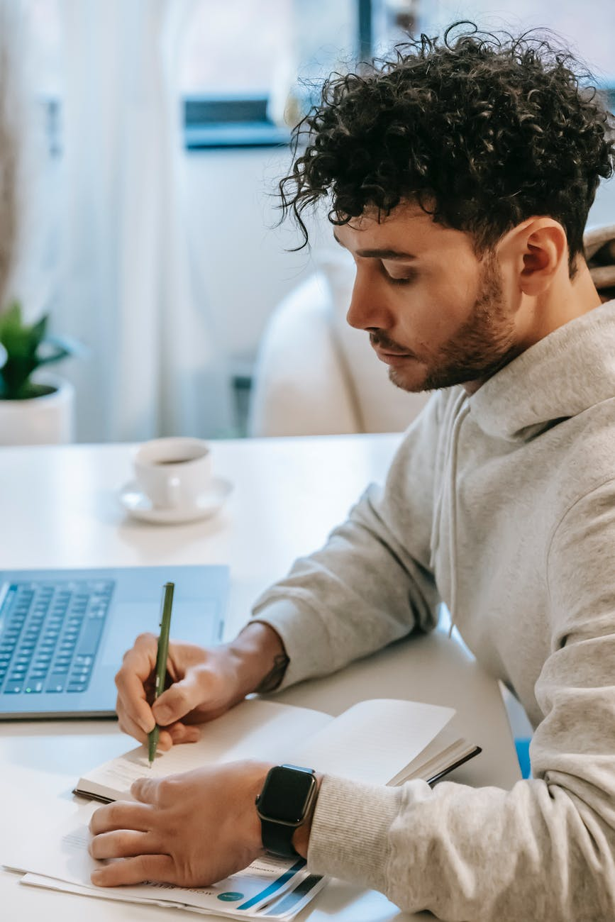 man taking notes in notebook near laptop and coffee cup. Photo by William  Fortunato on Pexels.com