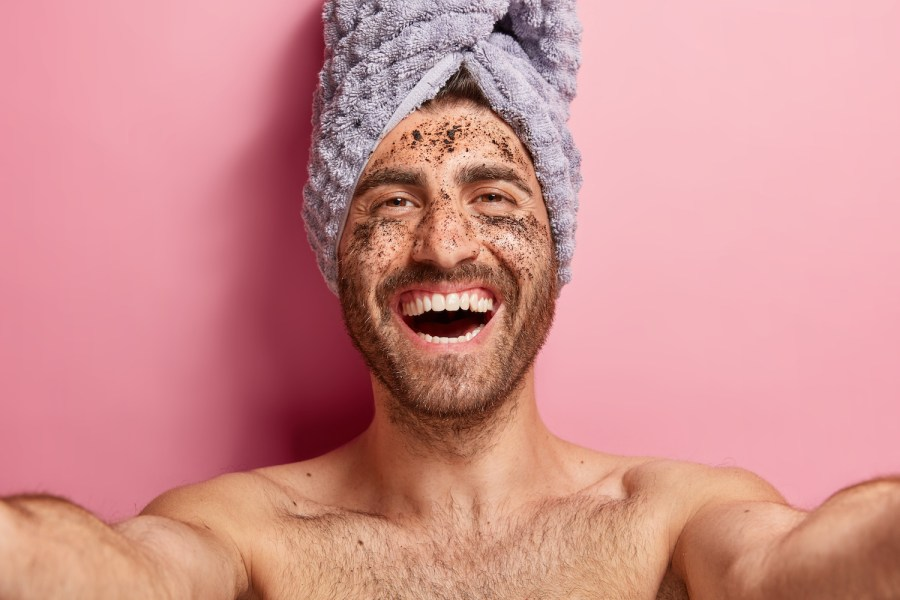 Acne Scars Types Treatments Prevention Natural Remedies. Healthy positive man makes selfie, applies coffee scrub on face skin, has cleansing procedures, poses topless against pink background with towel on head. Cosmetology, masculinity, beauty concept