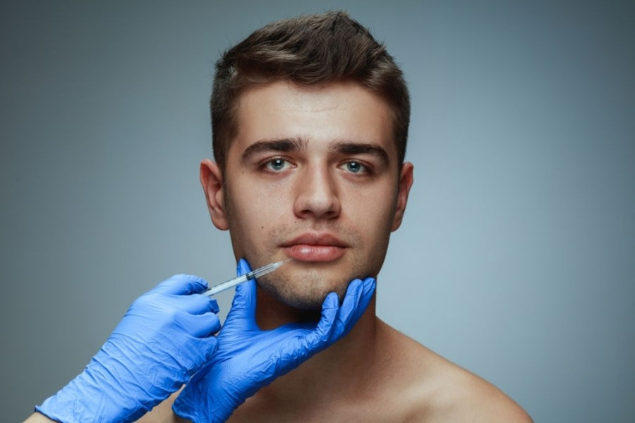 Close-up portrait of young man isolated on grey studio background. Filling botox surgery procedure. Concept of men's health and beauty, cosmetology, self-care, body and skin care. Anti-aging.