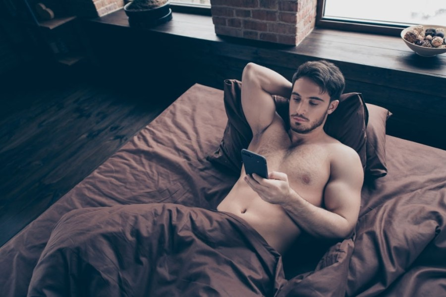 Close up high angle top view above photo of comfortable laying on red sheets linen he him his pretty man attention in telephone sms conversation not smiling