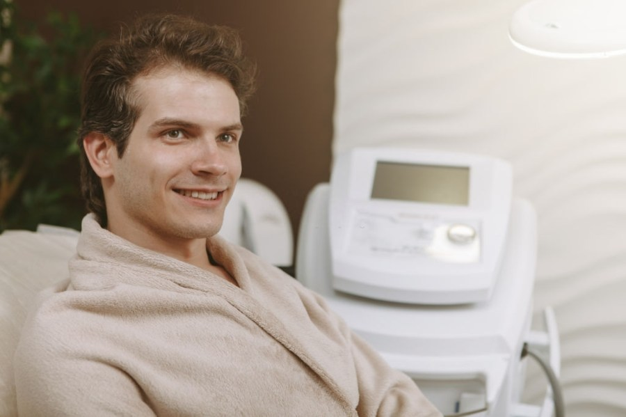 Microdermabrasion for Men: Everything You Need To Know  Close up of a happy healthy handsome man relaxing at spa center, wearing toweling robe, copy space. Relaxed cheerful man resting at spa recreation resort, looking away dreamily