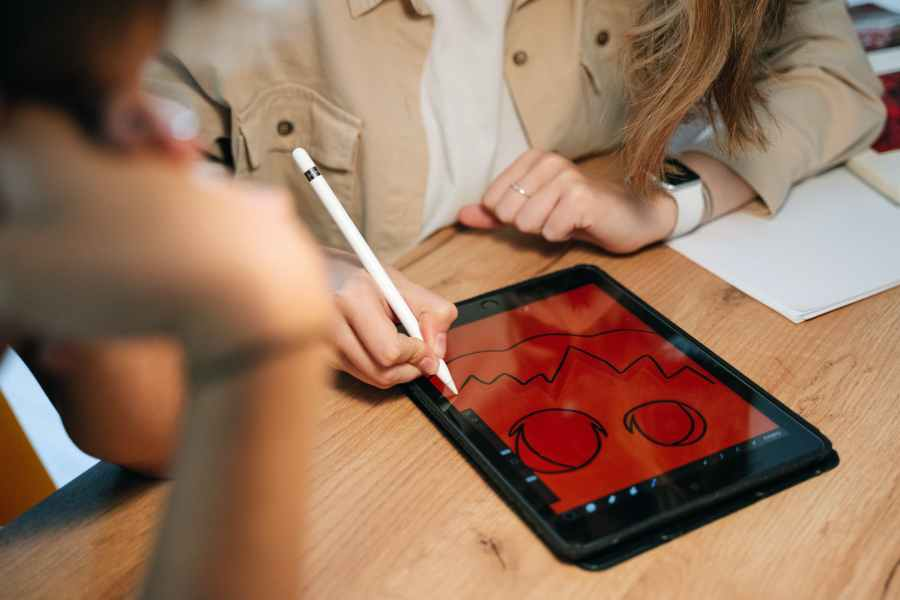 person drawing a jack o lantern on a tablet