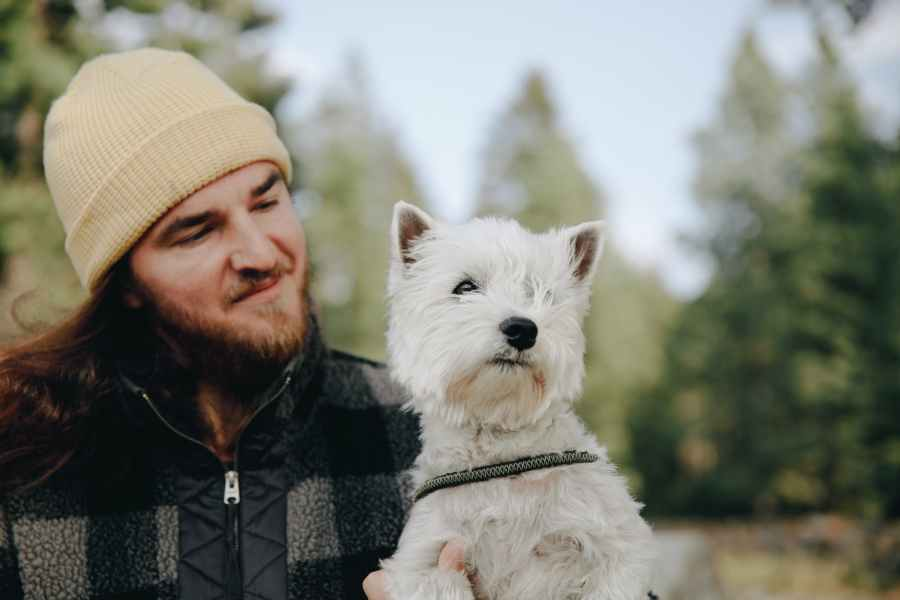 man wearing a cream knit cap holding a cute west highland white terrier