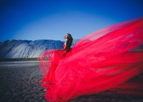 Beautiful woman standing in mountains. Wind blow. Red dress.