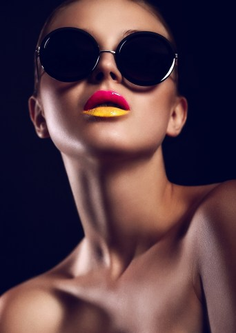 High fashion look.glamor closeup portrait of beautiful sexy stylish mode in sun glasses with bright colorful lips with perfect clean skin in studio