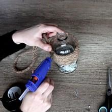 Gluing twine on upcycled liquor bottle