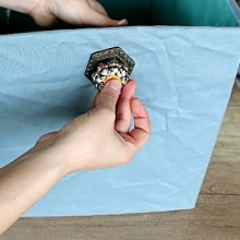 DIY storage bin covered with fabric and with a drawer knob