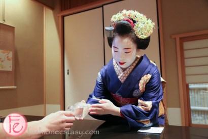 Kamishichiken maiko Ichitaka pouring sake for guest