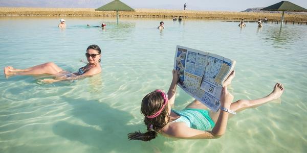觀光客在死海仰躺看報紙