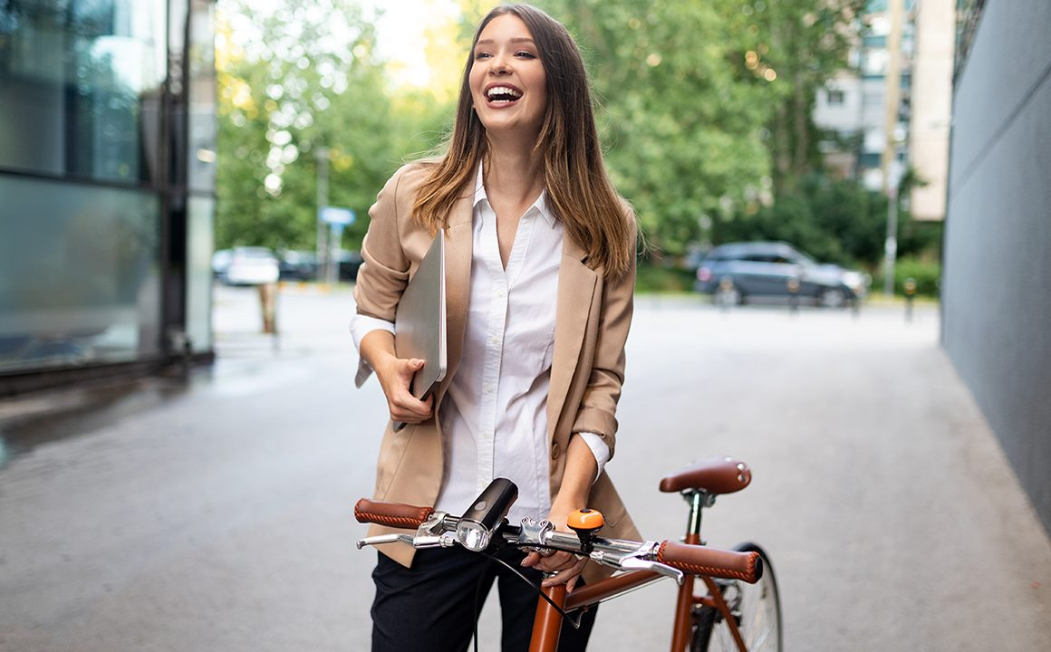 Happy business woman with bicycle to work on urban street in city. Transport and healthy lifestyle concept