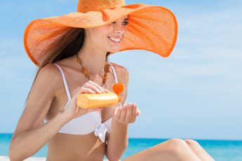 woman-applying-hand-cream-lotion-on-the-beach