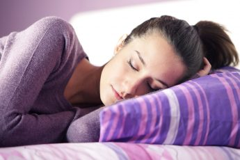 is-sleep-really-the-magical-cure-happy-woman-sleeping-in-purple-pajamas-main-image