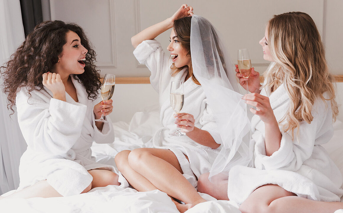 dream-wedding-venues-in-nyc-bridesmaids-hanging-out-with-bride-drinking-champagne