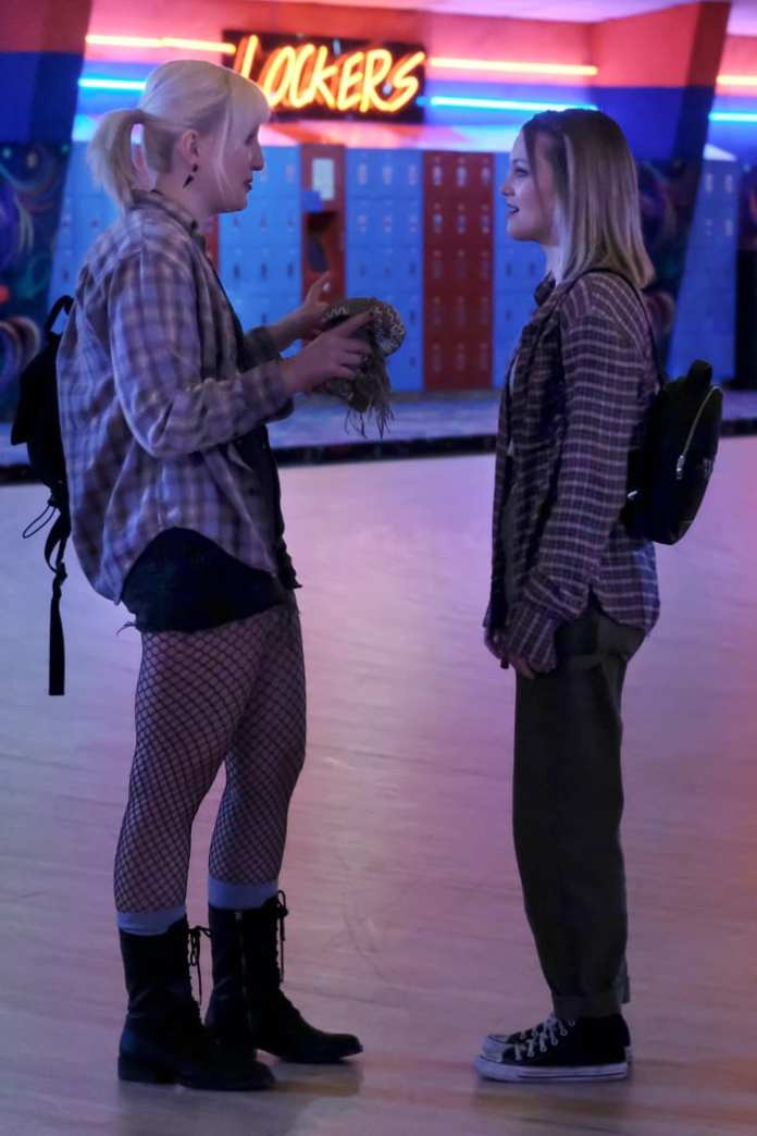 A Mallory and Kate (Olivia Holt) in quintessential '90s grunge at the skating rink.