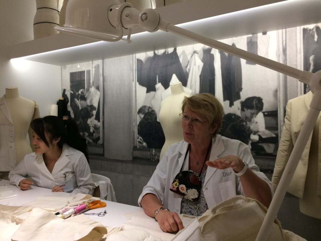 One of the workers in the atelier explains the process of making couture