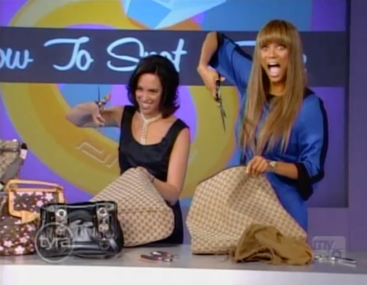 Professor Susan Scafidi and supermodel Tyra Banks standing with scissors to cut authentic and fake Gucci bags