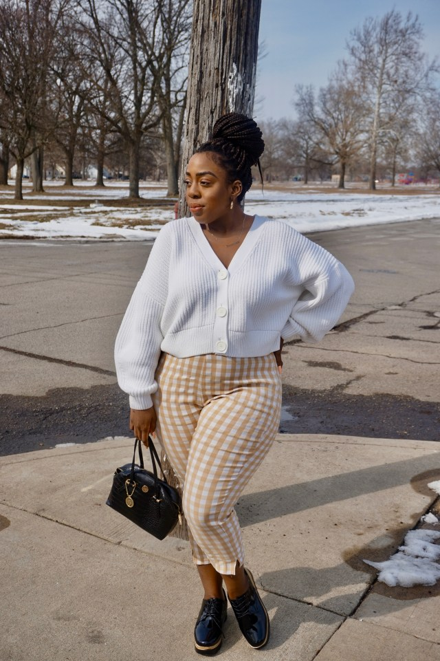 Black woman in cardigan sweater with taupe gingham pants