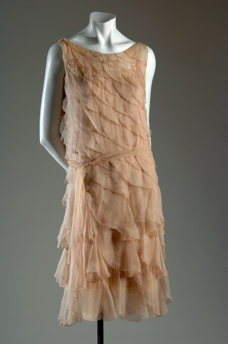 Evening chemise in pale pink crepe chiffon, straightline with graduating scalloped diagonal flounces; low open round neck with narrow shoulder straps, below knee length; self tie belt with picot edge