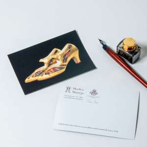 Postcard with golden shoes