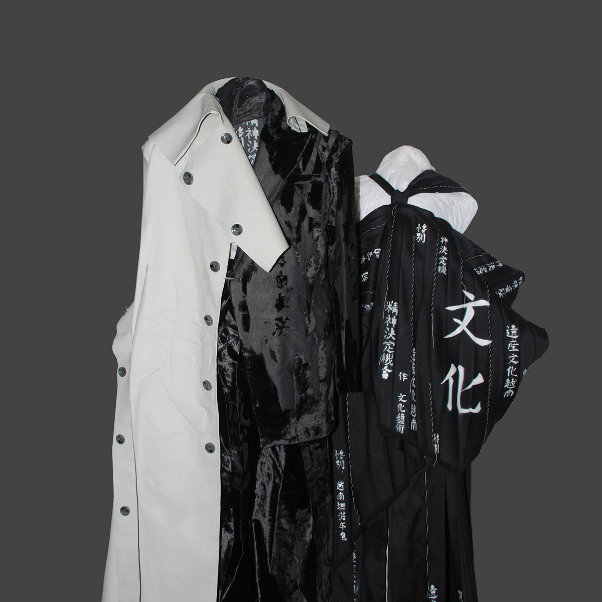 Trompe l'oeil latex trench coat with burn-out velvet suit and drape pleated top.