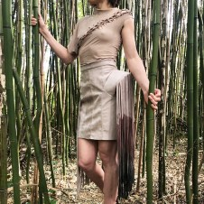 Asymmetrical skirt containing one structured hip and one flat saddle pocket with fringe.