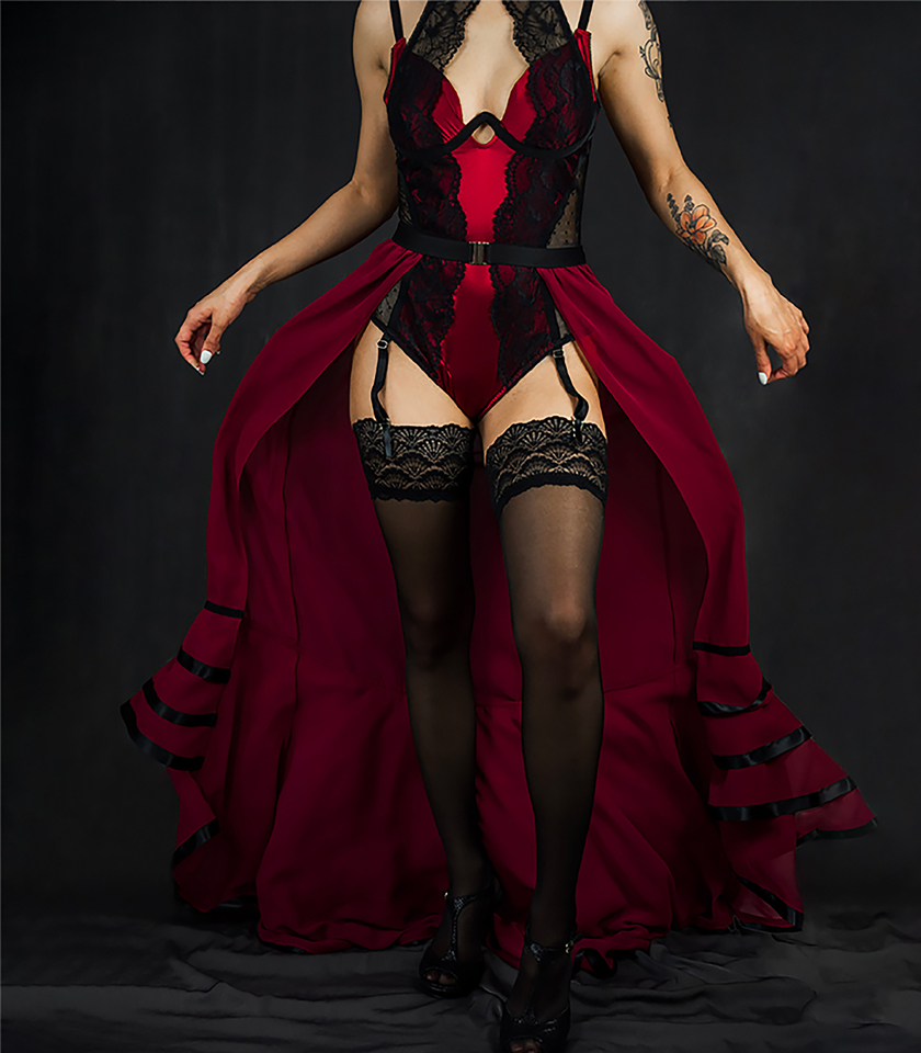 A full front view of this glamorous red bodysuit is made of silk charmeuse, black lace, and dotted mesh. The bodysuit features a keyhole neckline with a high-neck lace overlay. It is paired with a red chiffon skirt that has ruffles at the bottom and finished with black satin ribbon.