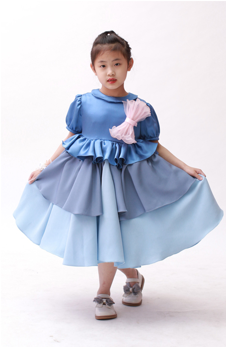 Little girl model standing and holding the sides of her blur dress out to show the full sweep.