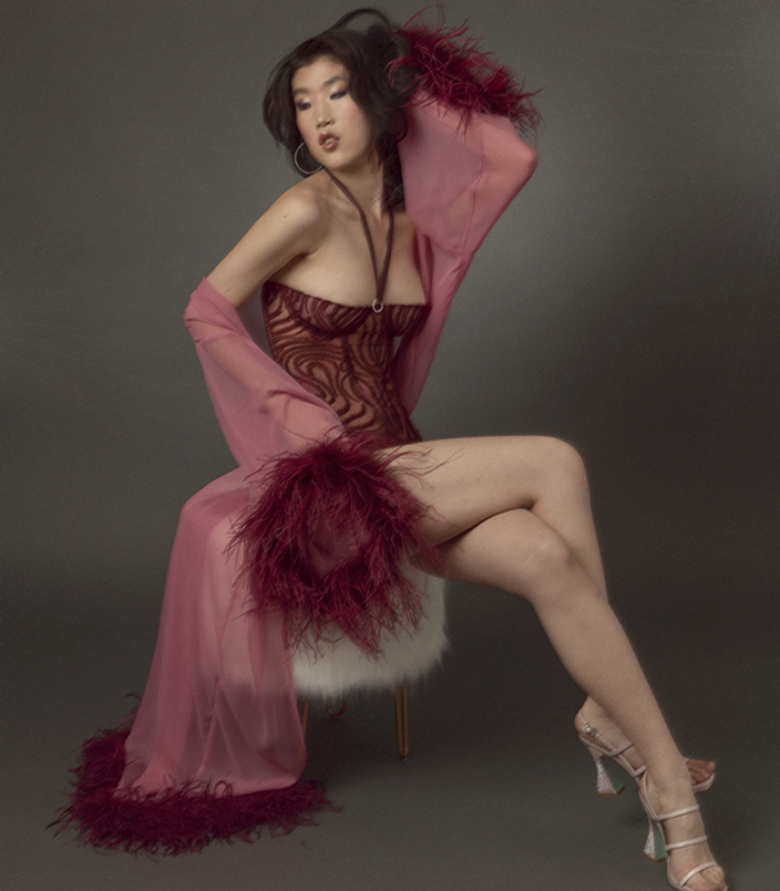 woman sitting on a white fur stool wearing a burgundy embroidered tulle bustier, silk panty with rhinestone details, and a pink silk chiffon robe with burgundy ostrich feather trim.