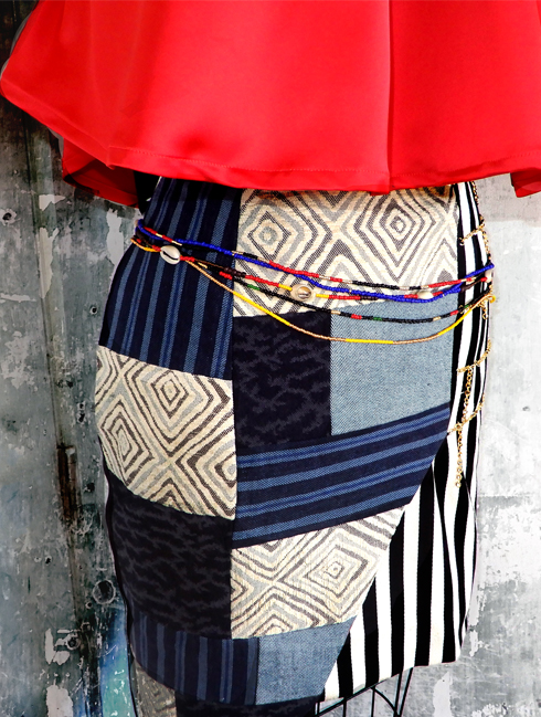Close-up detailed shot of patch-worked wrap skirt with waist beads attached.