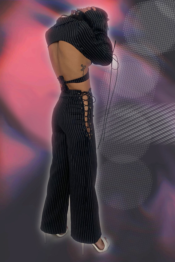 Back view of pinstriped power suit. Lace up on side seam for the wide leg pants and blazer has an open back with a tie up closure.