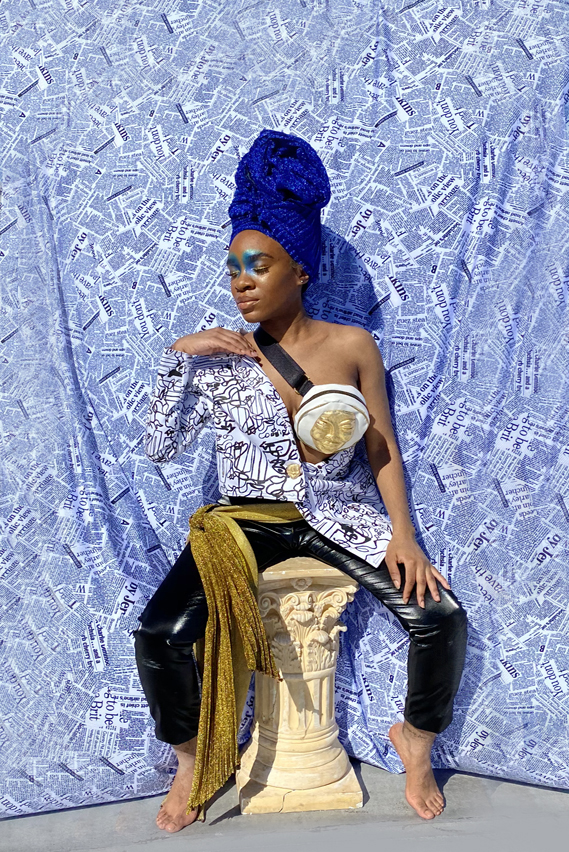 Woman seated on a column in shimmer blue head wrap. Abstract black and white print asymmetrical blazer. Black faux leather pants with golden glitter waist sash. Newsprint backdrop. Golden mask fanny pack accessory. Dramatic blue eyeshadow on inner eyelid and inner eyebrows.