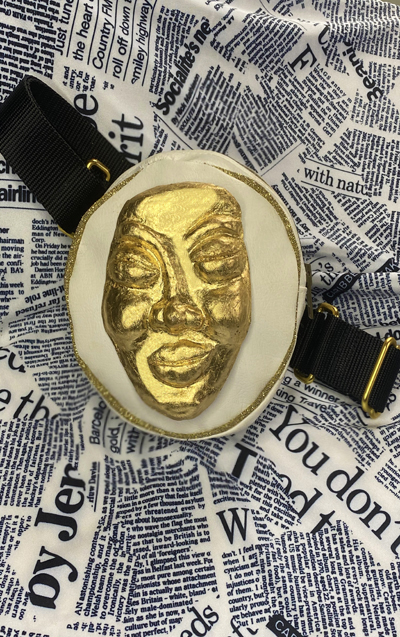 White leather round fanny pack with gold hardware details and black straps. Golden face mask detail placed in front.
