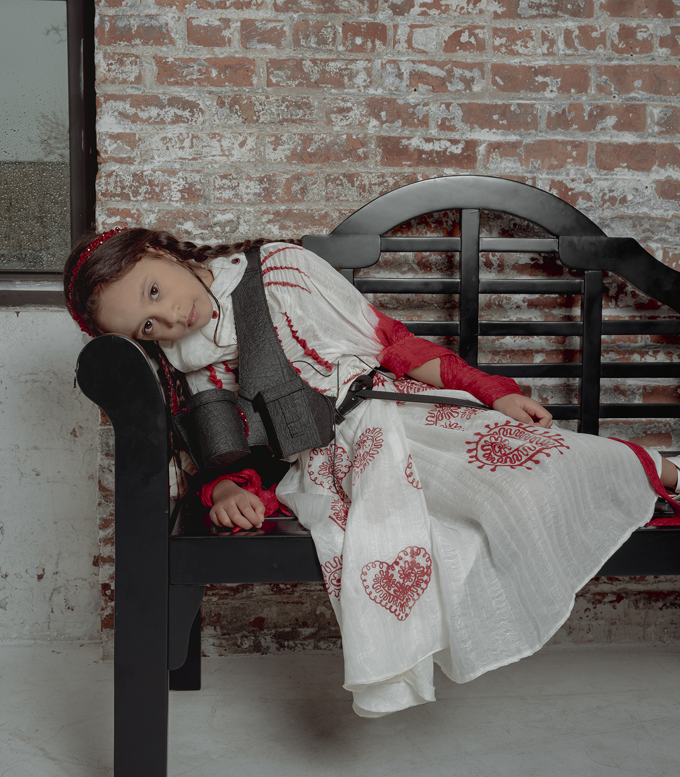 An eight-year-old brown hair girl leaning on a black bench wearing a high neck white silky blouse and a red heart pattern printed box pleat skirt and a black vest, a background of brick wall and rainy windows.