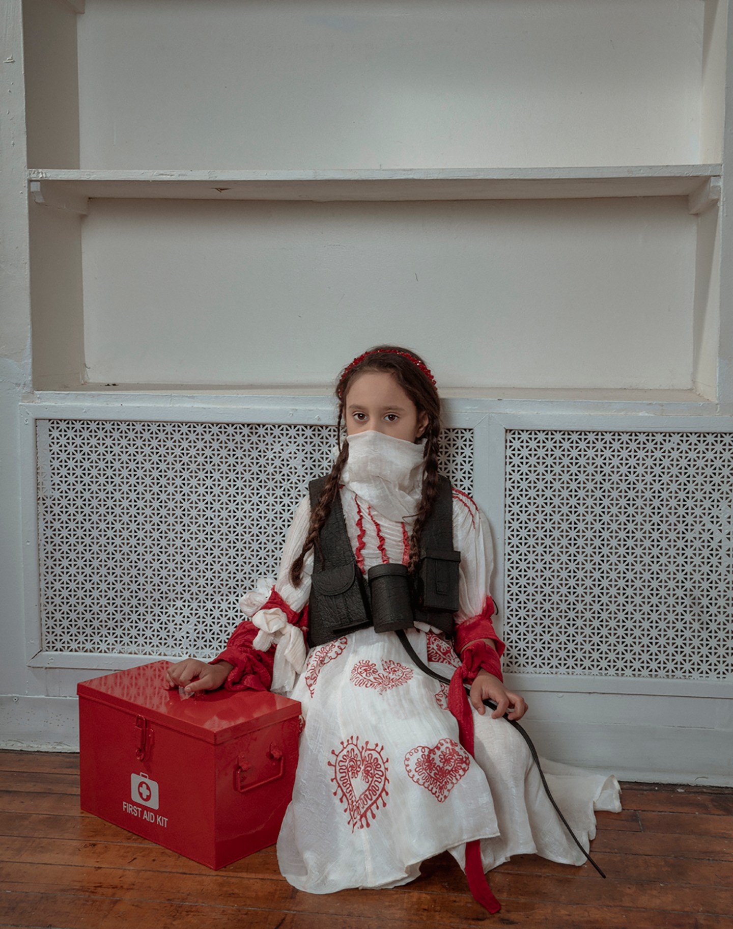 An eight-year-old brown hair girl holding a first-aid box, wearing a high neck white silky blouse covering her face, a red heart pattern printed box pleat skirt, and a black bullet vest. The girl is sitting on the floor looking straight.