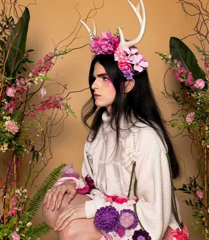 Nonbinary person crouching. Wearing floral crown with antlers, and ivory knit dress embellished with yarn flowers.