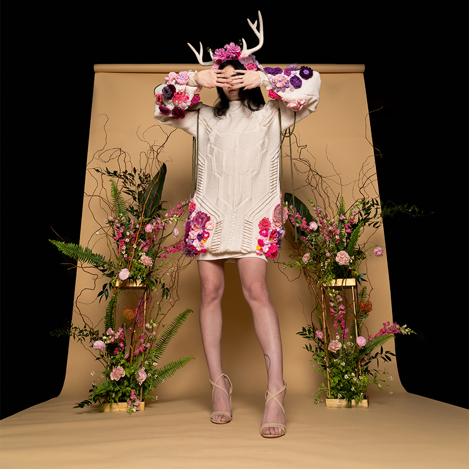 Nonbinary model standing with hands covering face. Front of sweater dress shows knitted motif of a deer skull with knitted cord texture framing the skull. The cords are framed by densely-applied yarn flowers in shades of pink, purple, and yellow. Model wears flower crown embellished with silk flowers and faux antlers. Green knitted cord hangs from arms.