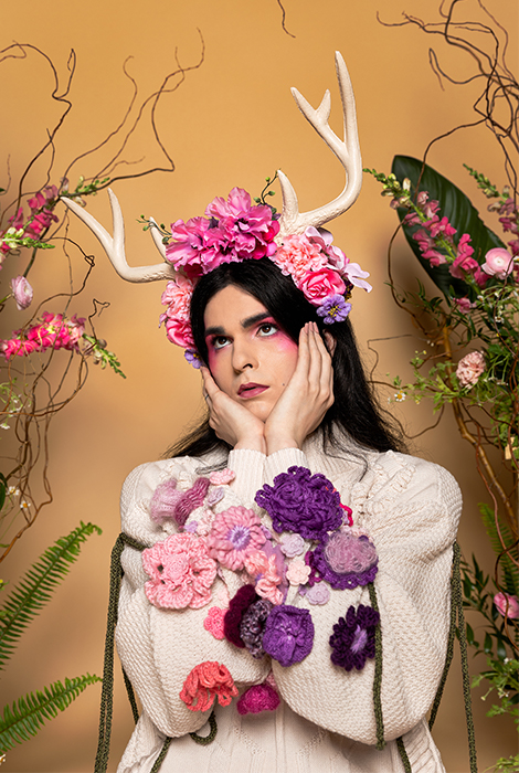 Nonbinary model looking up, resting head in their hands. Left and right sleeves pressed together blend the purple and pink yarn flowers from both sleeves. Model wears flower crown embellished with silk flowers and faux antlers. Green knitted cord hangs from arms.