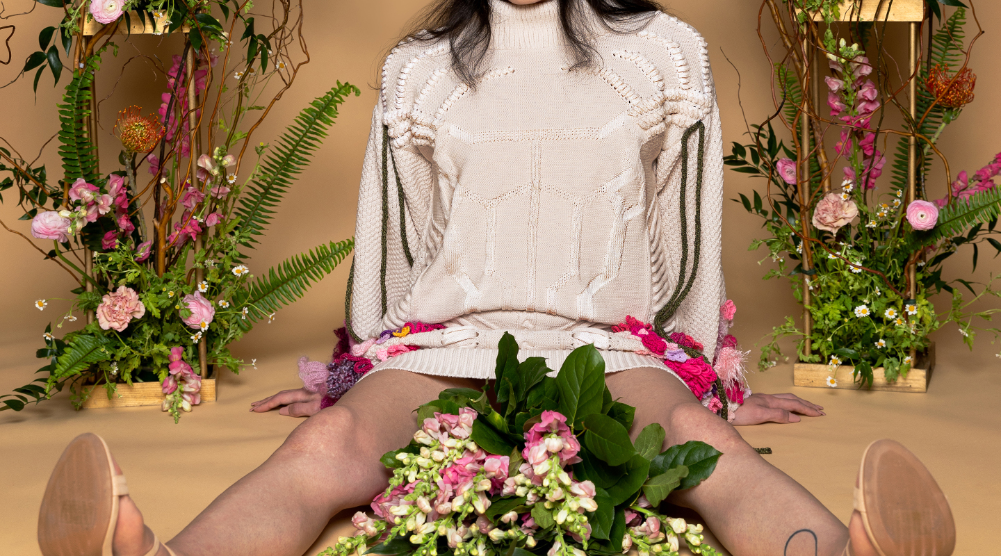 Model sitting on ground with spread legs, framing a bouquet of fresh flowers. Head cropped, showing shoulder detail of knitted cord woven into sweater, creating antlers for deer skull motif. Green knitted cord hangs from shoulder seams.